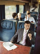 Businessman using mobile phone on train (focus on man)