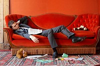 Businessman asleep on sofa surrounded by toys