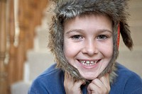 Boy (7-9) wearing trapper´s hat, smiling, close up, portrait