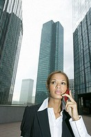 Businesswoman using mobile phone by skyscrapers