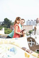 Couple leaning on wall at edge of rooftop terrace, smiling