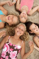 Four girls (8-12) lying in circle on beach, holding hands, portrait