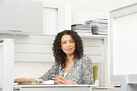 Mature businesswoman sitting at desk, smiling, portrait