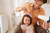 Father blowdrying daughter´s (2-4) hair in bathroom, close-up