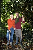 Young couple standing holding garden fork and rake, smiling, portrait