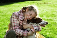 Girl (7-9) hugging dog, smiling