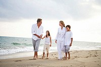 Family walking on beach, smiling, children (7-9)