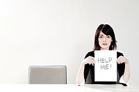 Businesswoman holding a 'Help Me' sign