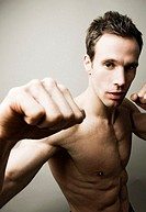Shirtless man striking a kung fu pose for the camera