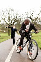 Businessman trying to beat another businessman with an umbrella (thumbnail)