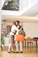 mature couple embracing man holding orange bag