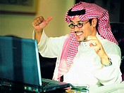Happy Saudi businessman in front of his laptop