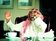 Happy Saudi businessman using telephone