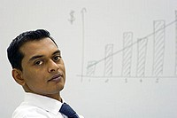 Indian Businessman in front of a whiteboard with graph showing growth