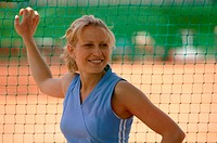 Female Tennis Player Holding Net