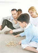 Family playing pick-up-sticks on floor