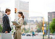 Young business associates standing on street corner, talking