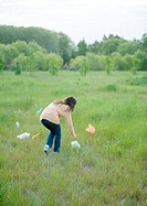 Woman picking up plastic bags in field