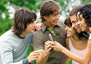 Group of young friends looking at cell phone