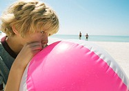 Boy blowing up beach ball at beach
