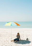 Boy sitting on beach under parasol