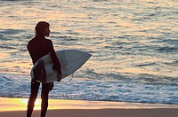 After a long day surfing a young surfer is watching the sunset over  the Pacific Ocean, Baja California, Mexico