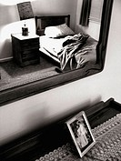 A bedroom s captured in black and white from the perspective of shooting into a mirror