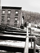 Worn steps and an old brick tenement building are captured during the winter in New England