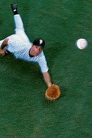 High angle view of a baseball player diving to catch a baseball