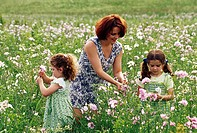 Mother with her two daughters picking flowers in a field
