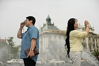 Heterosexual Asian couple taking pictures in front of a fountain