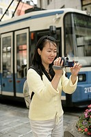 Young Asian woman with a camera standing in front of a tramway, selective focus