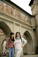 Two young Asian women standing in front of a painted gate, selective focus