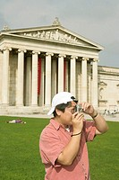 Asian man with a camera standing in front of an antique museum