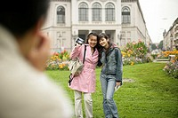 Man taking a picture of two Asian women who are standing on a meadow in front of buildings, selective focus