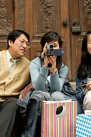 Two young Asian women and one Asian man with shopping bags and a camera sitting in front of the wooden door of a church