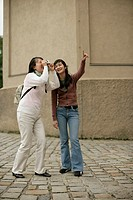 Young Asian woman pointing at something while another woman is taking a picture of the shown place