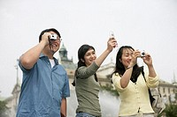 Three Asian people taking pictures, low angle view