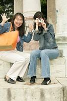 Two Asian women sitting on the stairs of a monument, one of them with a camera in her hand