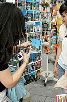 Young Asian women next to a man grasping a postcard from a rack, selective focus