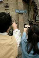 Two Asian people pointing at a sign saying 'Marienplatz'
