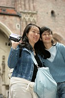 Two Asian women standing in front of an medieval building, selective focus