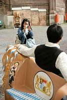 Asian woman taking a picture of a man who is leaning against the figure of a lion, selective focus