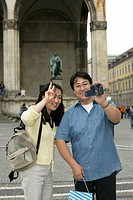 Asian man filming himself and his wife with a camera while they are standing in front of a monument, selective focus