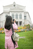 Young Asian woman taking a picture of an ancient building, selective focus