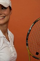 Smiling female tennis player holding a racket