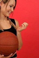 Young woman holding a basketball in her hand and looking at her finger nails