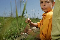 Boy sitting in a meadow, holding a blade of grass in his hand