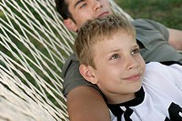 Father and son lying together in a hammock