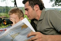 Father holding world map while his son is looking through binoculars
